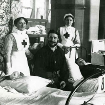 PATIENTS LIE IN BEDS WITH RED CROSS NURSES STANDING BESIDE THEM.